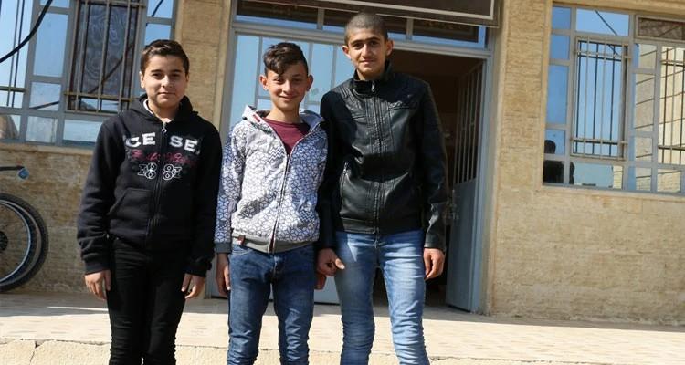 Noeh e alguns de seus amigos em frente a sua escola, em Karamles